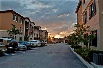 exterior of the community at sunset showing ample parking