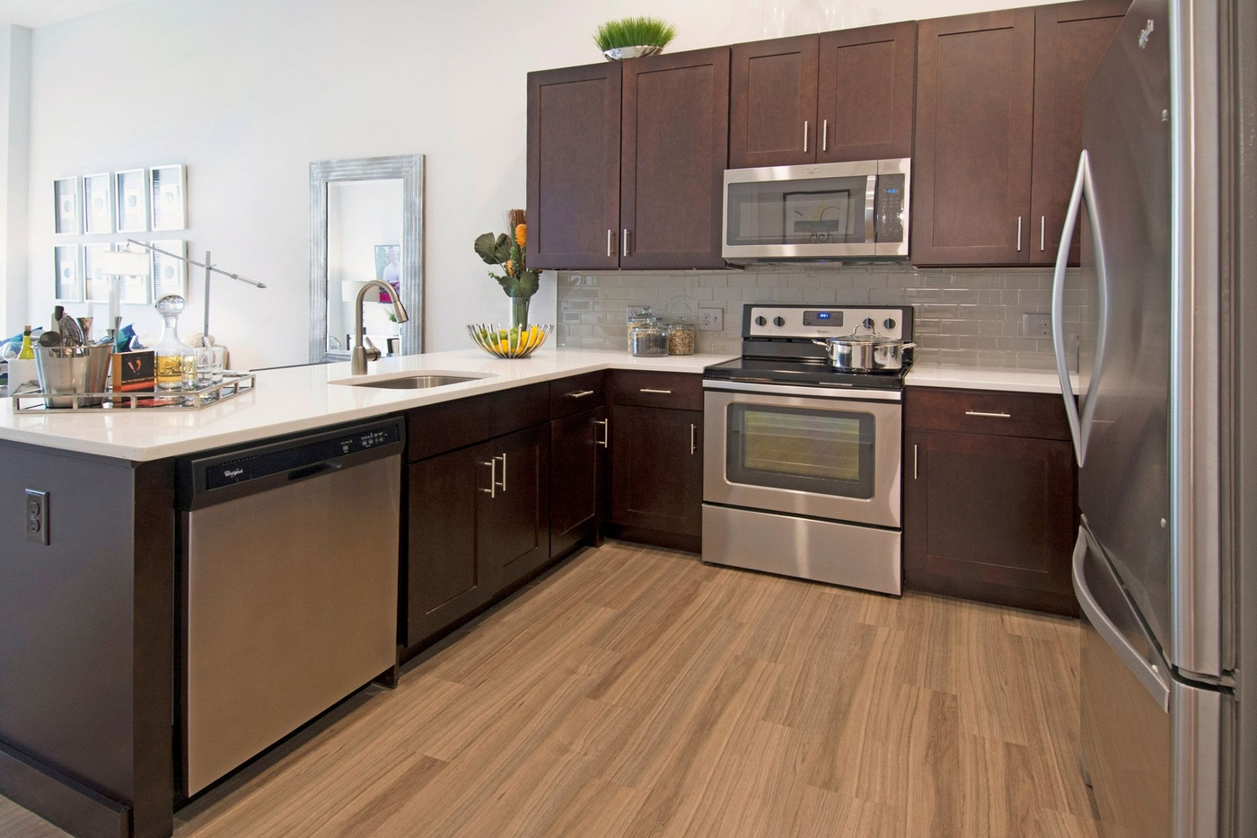 Interior image of apartment kitchen with wood floors, dark wood cabinets and stainless steel appliances