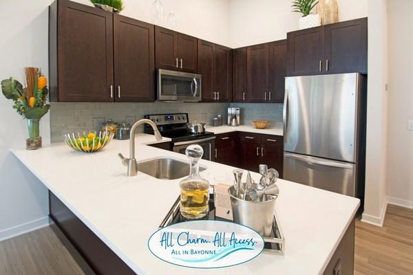Interior kitchen with dark wood cabinets, stainless steel appliances