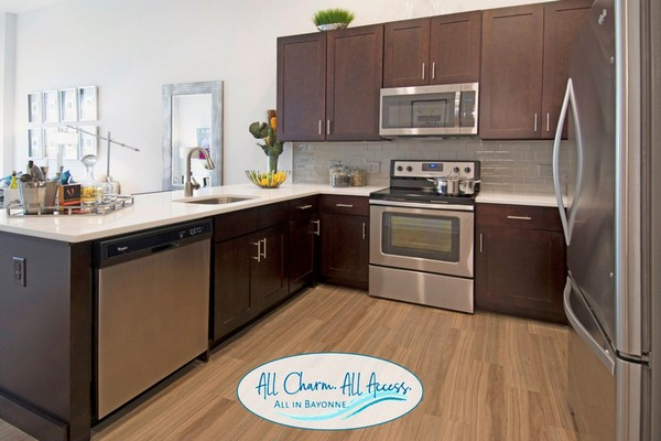 Interior image of kitchen, wood floors and stainless steel appliances
