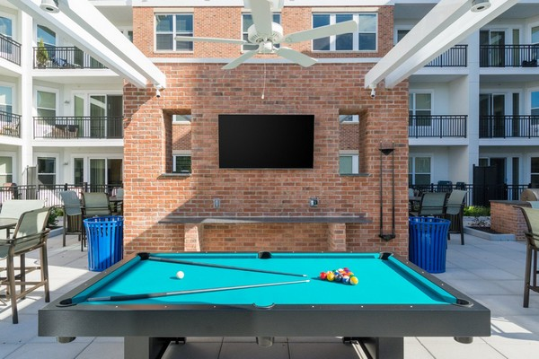 Outdoor image of grilling station, patio tables and pool tables
