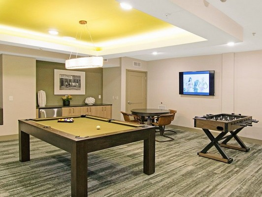 Interior image of community  game room with pool table, foosball and poker table