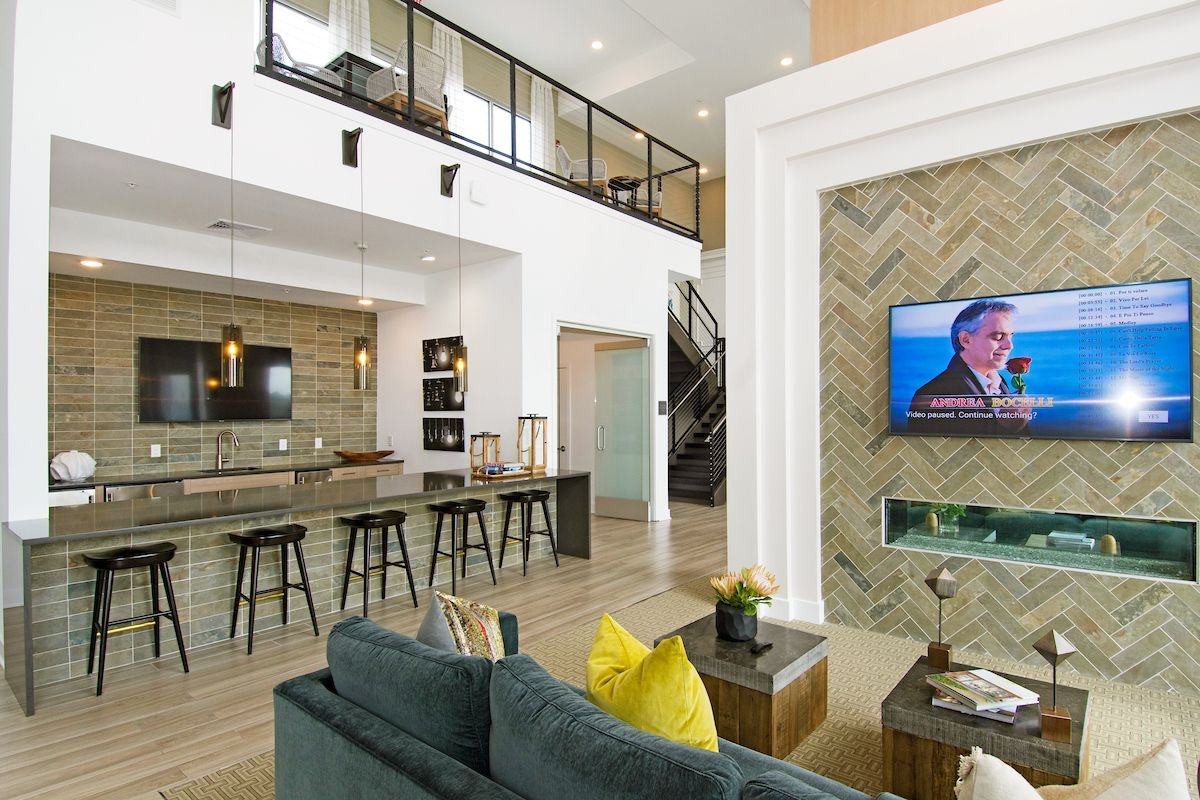 Interior image of club house with TV, kitchen couches and tables with chairs