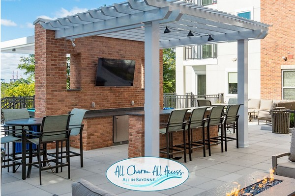 Exterior image of outdoor grilling bar with chairs and TV