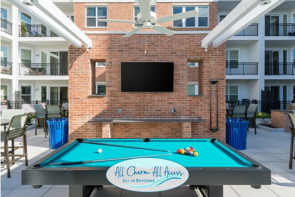 Outdoor image of pool table with TV and chairs