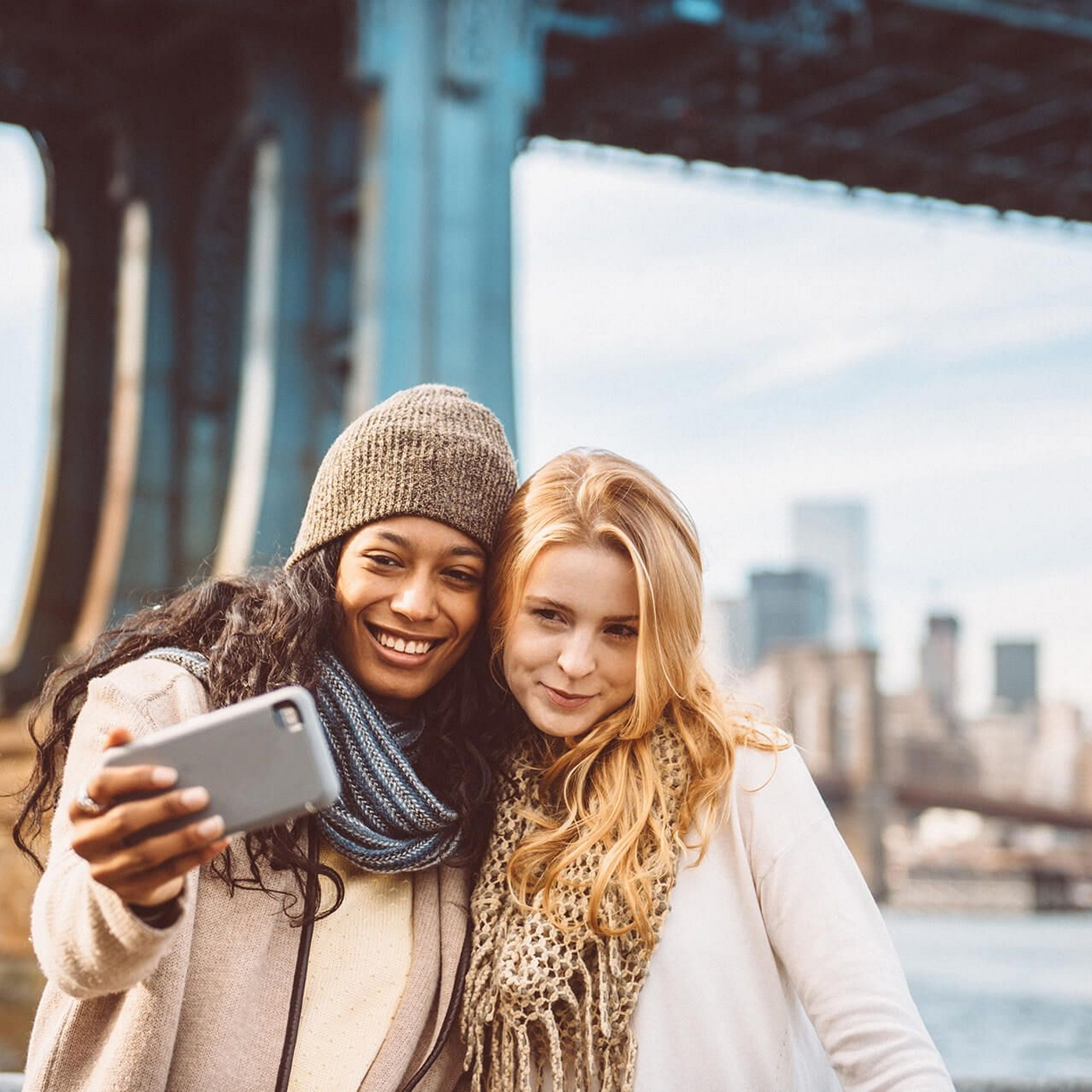 Image of two women taking a photo with city behind them