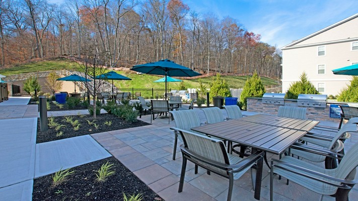 Outdoor image of patio and grilling area with umbrella tables
