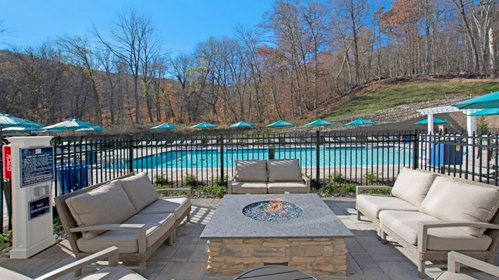 Outdoor image of firepit and lounge chairs next to pool.