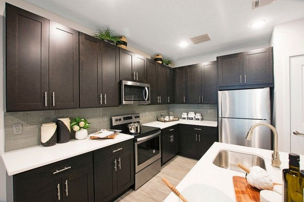 Interior image of kitchen, island, dark wood cabinets and stainless steel appliances