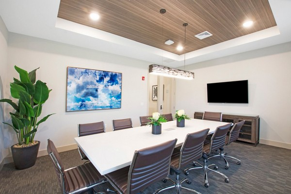 Interior image of community conference room with a large conference table with a large monitor