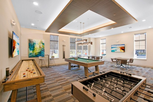 Interior image of community game room with foosball, shuffleboard and pool tables