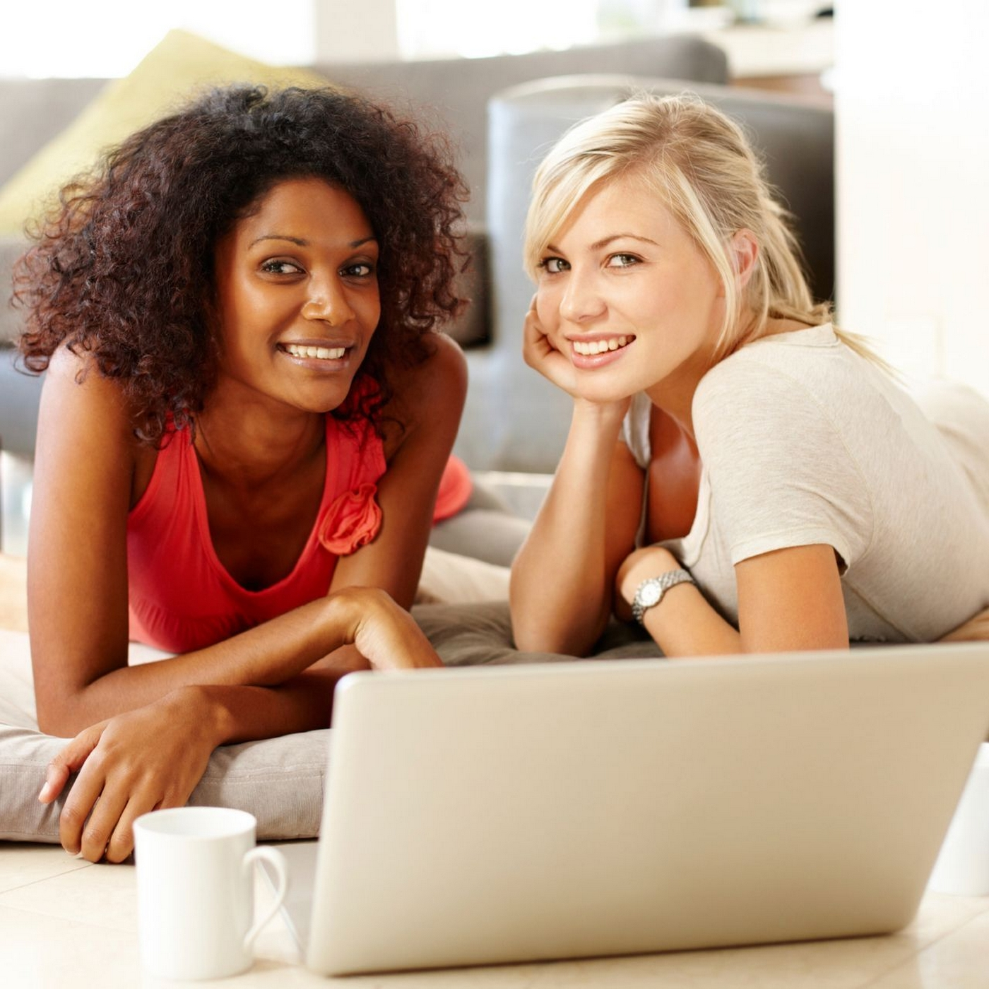 Image of two women laying on the ground on a laptop