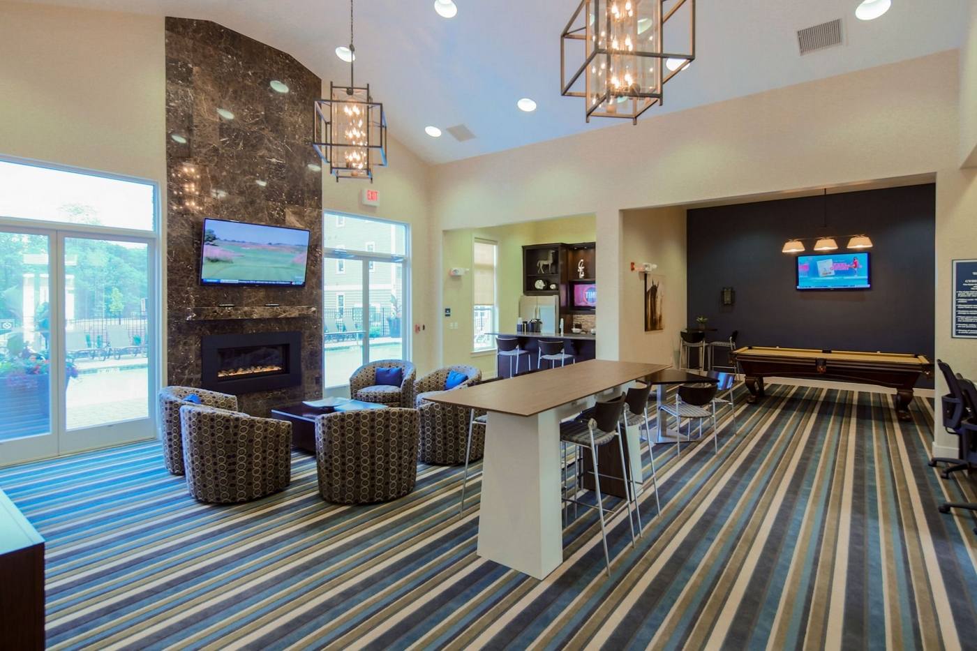 Interior image of club house with couches, fireplace, pool t