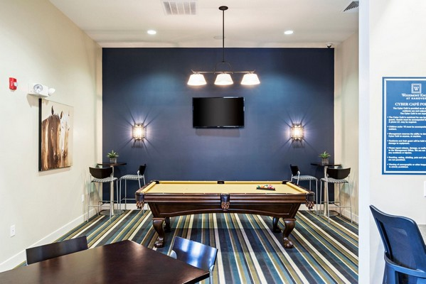 Interior image of club house with couches, tables, chairs and pool table