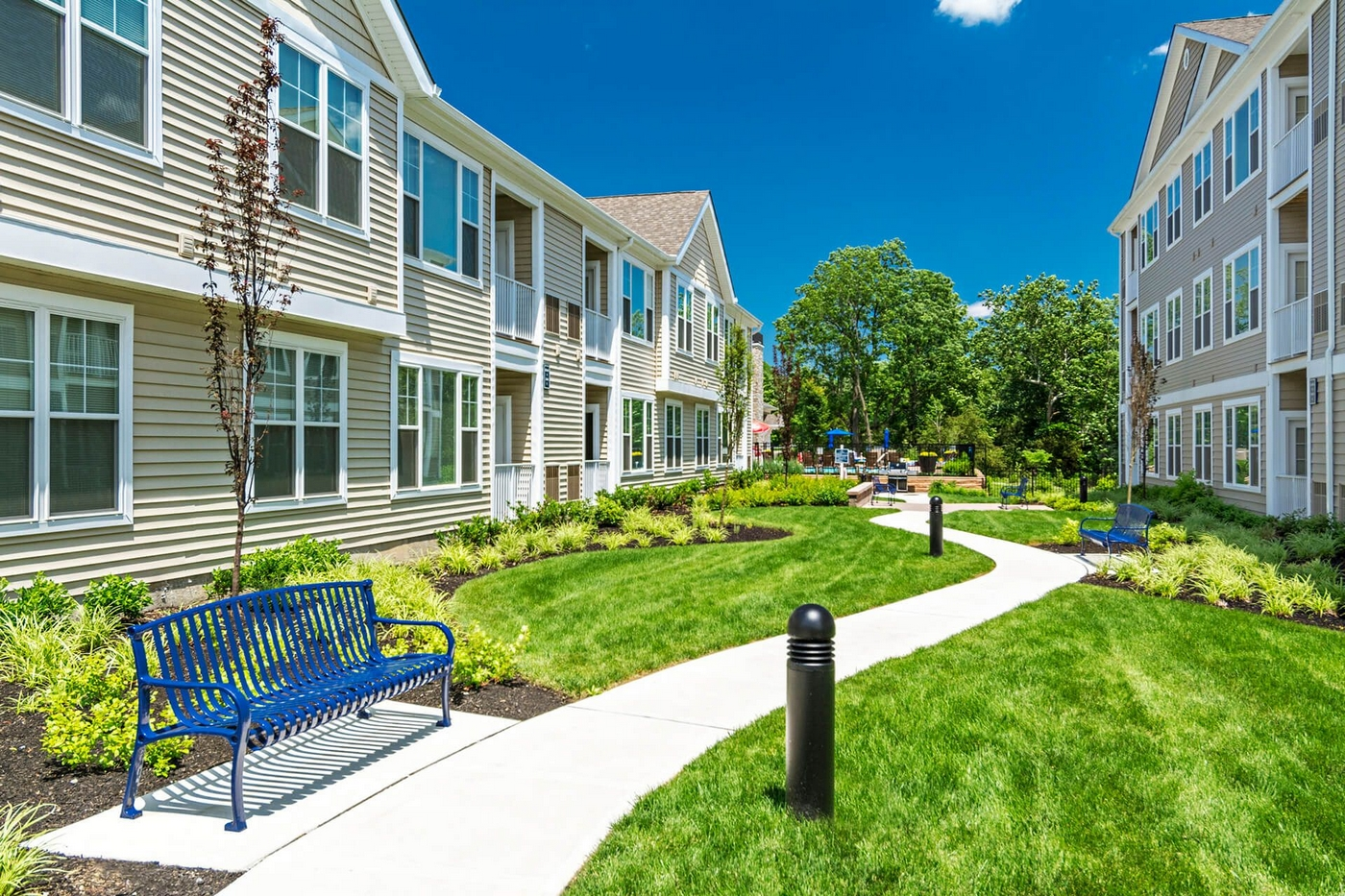 Exterior image of apartment unit with landscaped grounds walkway