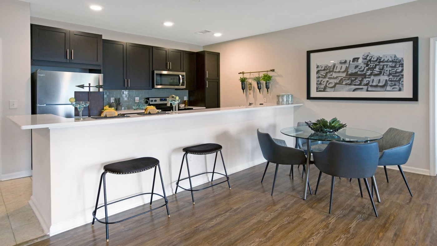 Interior image of apartment dining table and a large kitchen island. Dark wood cabinets and stainless steel appliances.