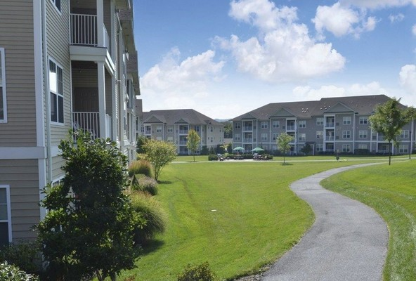 Outdoor image of apartment complex with landscaped grounds with a walkway through the community