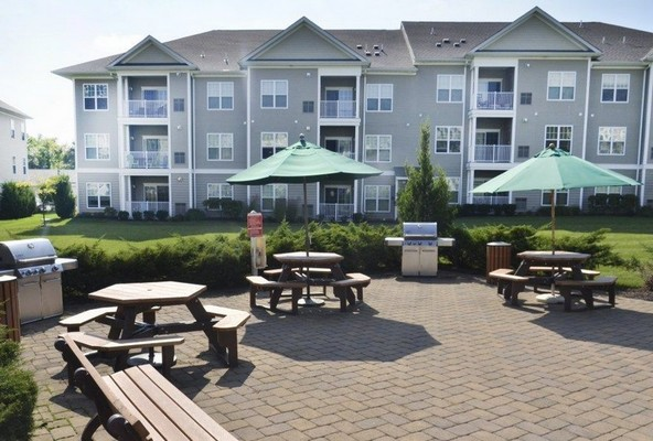 Outdoor image of community patio area with umbrella tables and chairs