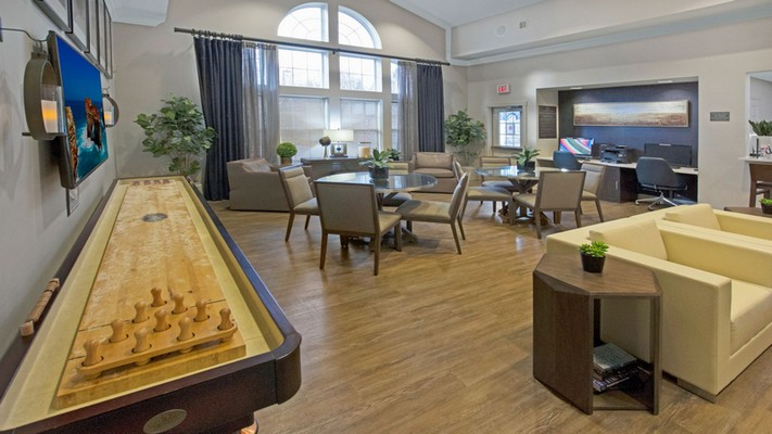 Interior image of community clubhouse with couches, tables, chairs and shuffleboard.