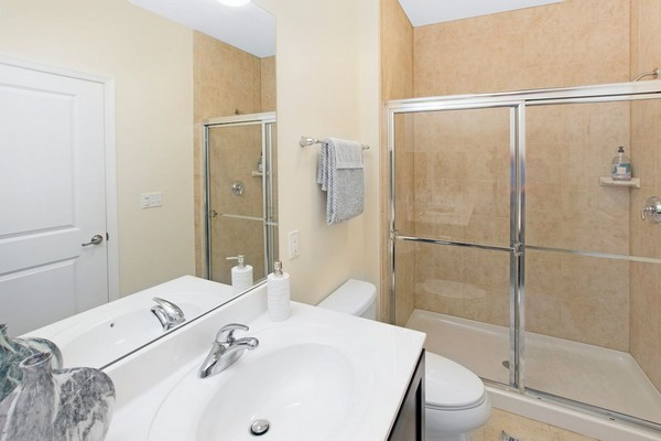 Interior image of apartment bathroom, white counter, tile floors and walk in shower