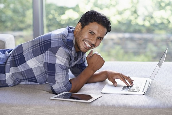 Image of man laying down working on a laptop