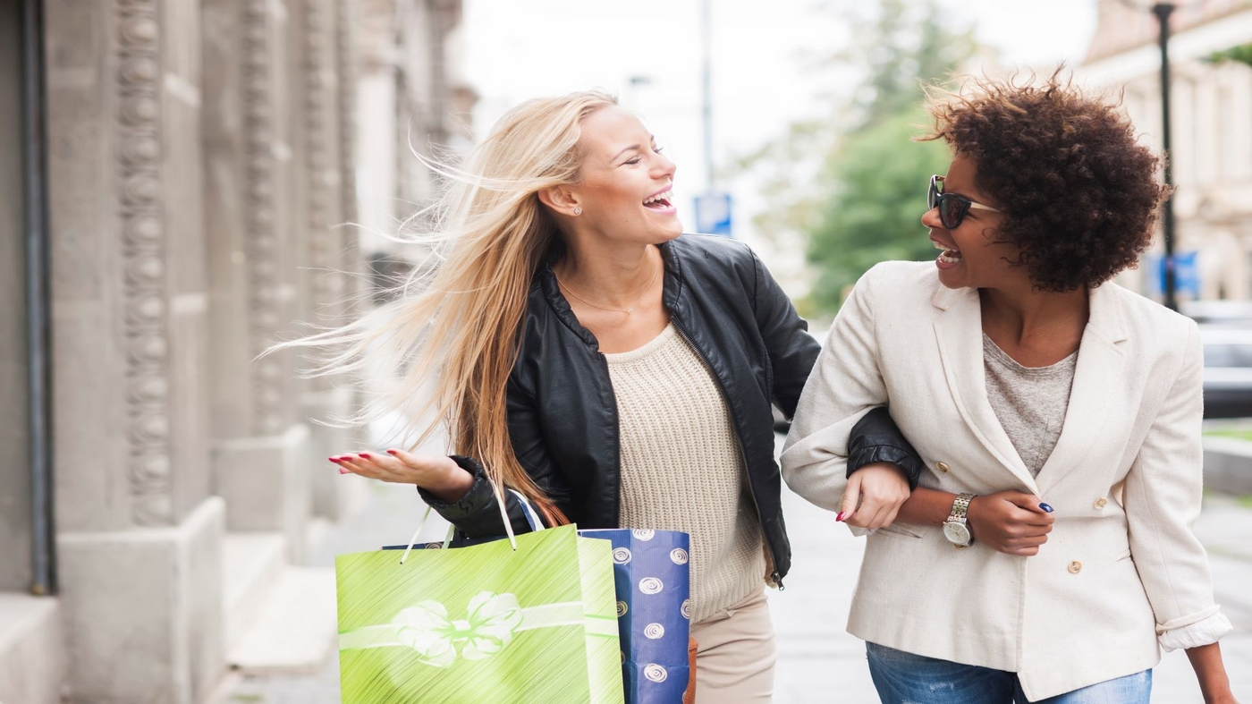 Image of two women shopping holding arms while walking down the street