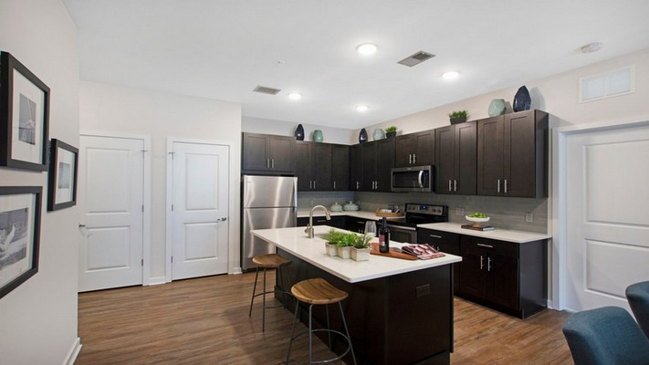 Interior image of kitchen with island, wood flooring, dark wood cabinets and stainless steel appliances