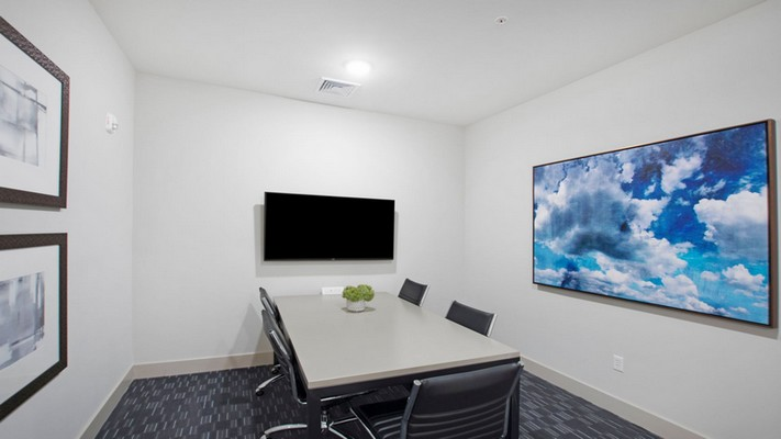 Image of community conference room with a display monitor and conference tables.