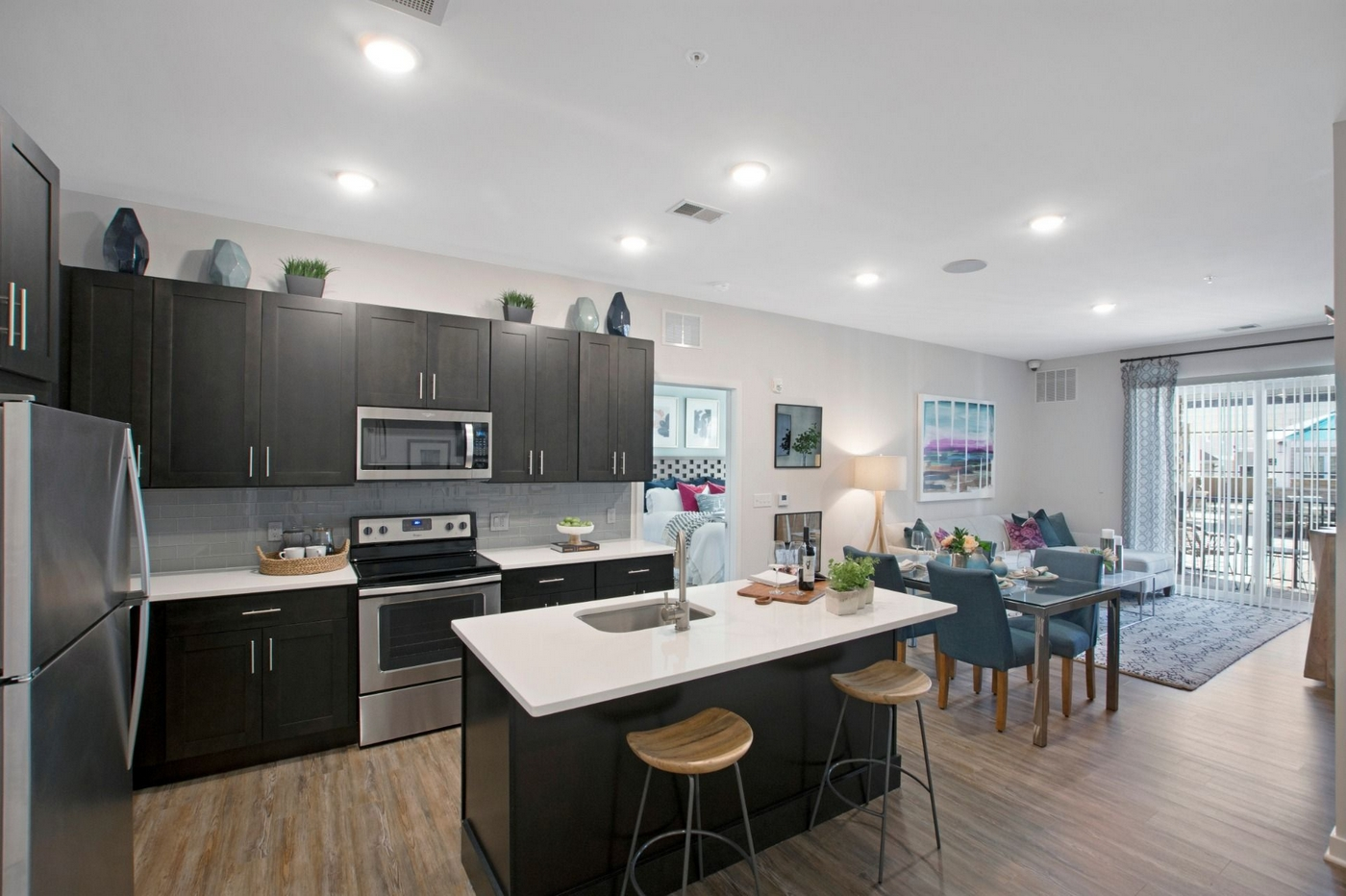 Interior image of kitchen, island, wood floors, dark wood cabinets and living room space