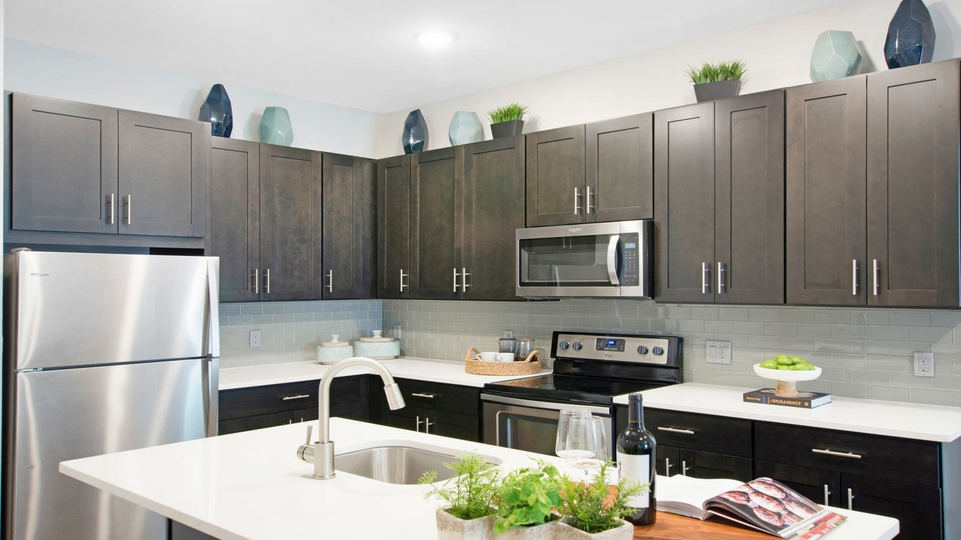 Interior image of kitchen, dining island, stainless steel appliances and dark wood cabinets