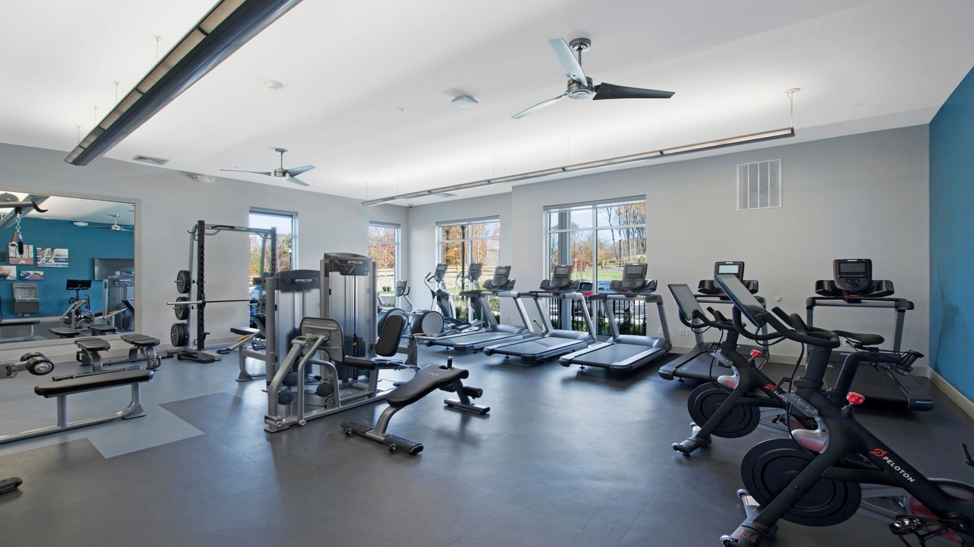 Interior image of onsite fitness room with cardio and weight lifting equipment