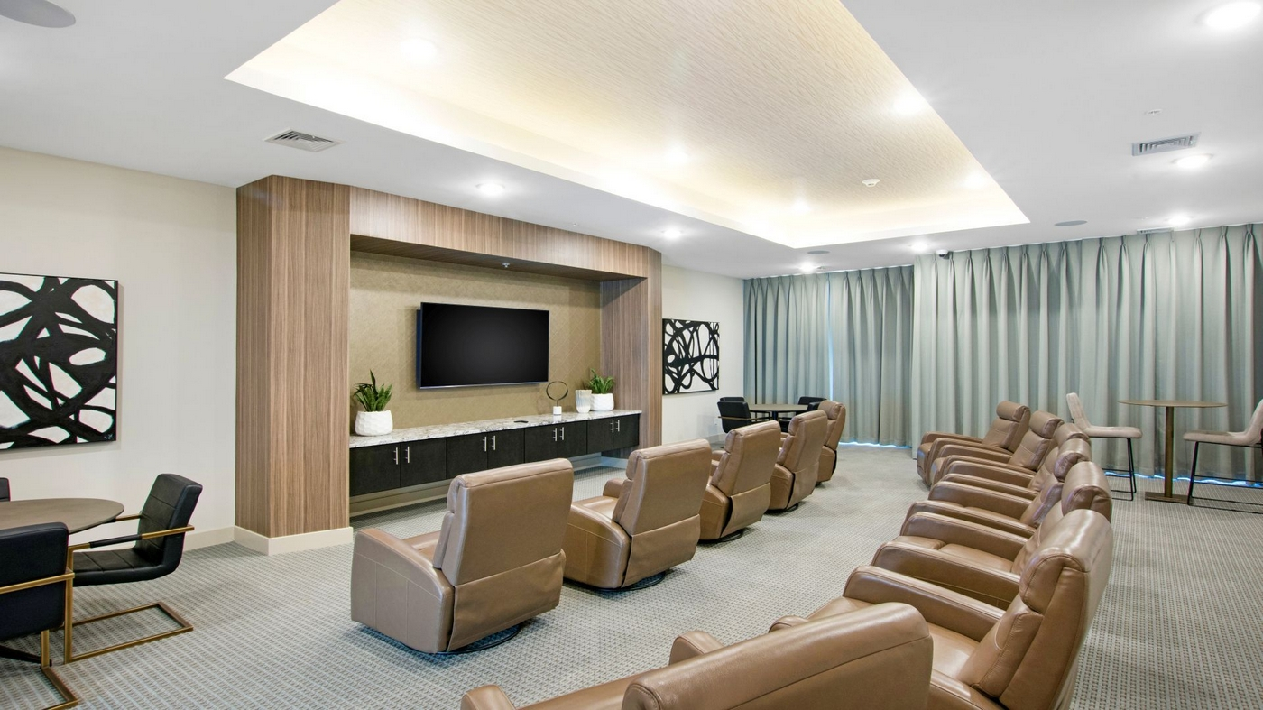 Image of community movie room with recliners and table with chairs