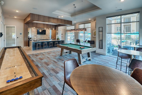 Interior image of community room with pool table, shuffleboard and bar kitchen