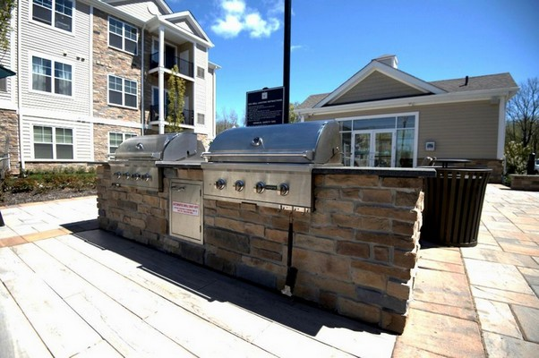 Outdoor image of grilling station and patio tables covered with umbrella