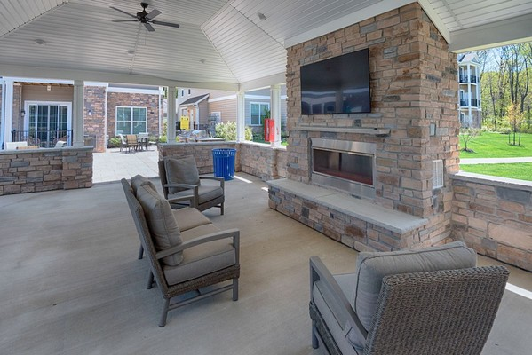 Outdoor seating with fireplace and television
