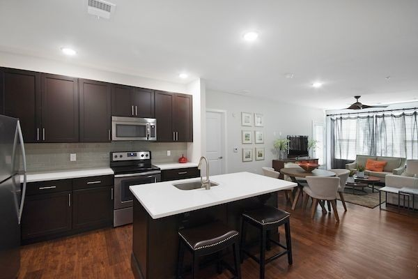 Apartment kitchen with island and view of living and dining area