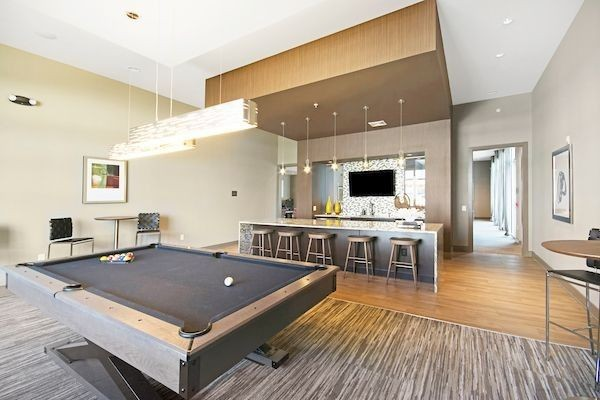 Clubhouse game room with billiards and bar area