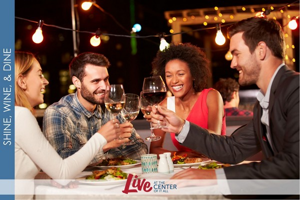 Outdoor photo of friends tapping wine glasses together at a dinner party