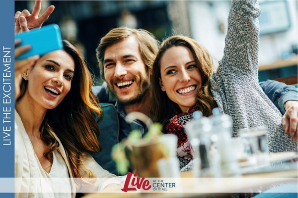 Image of friends taking selfies at an outdoor dining table