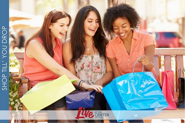 Outdoor image of three women holding shopping bags sitting on a bench