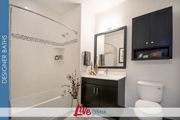 Interior bathroom image with vanity mirror and dark wood cabinets