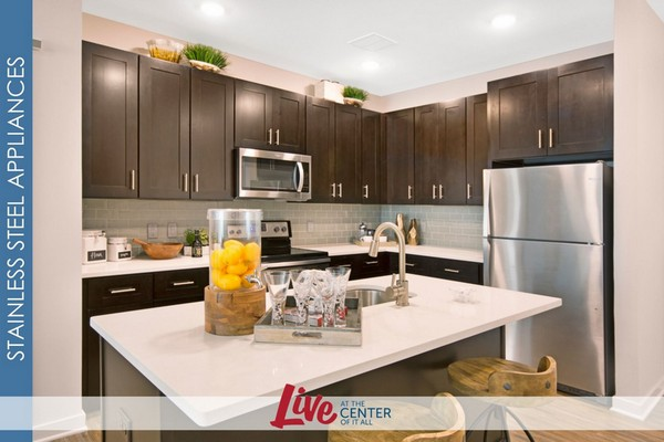 Interior image of kitchen, wood floors, stainless steel appliances