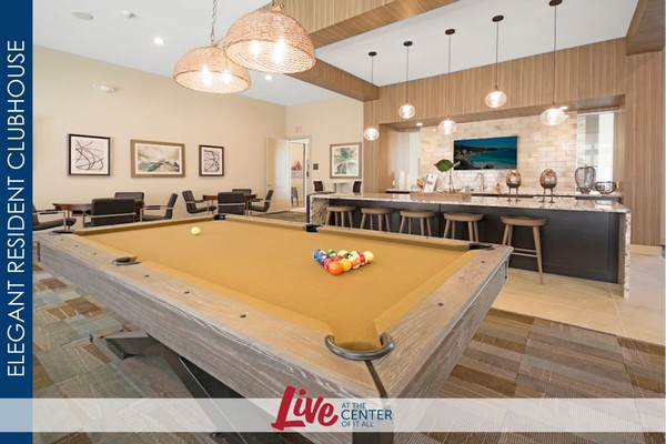 Interior image of resident game and entertainment room with pool tables and community kitchen bar