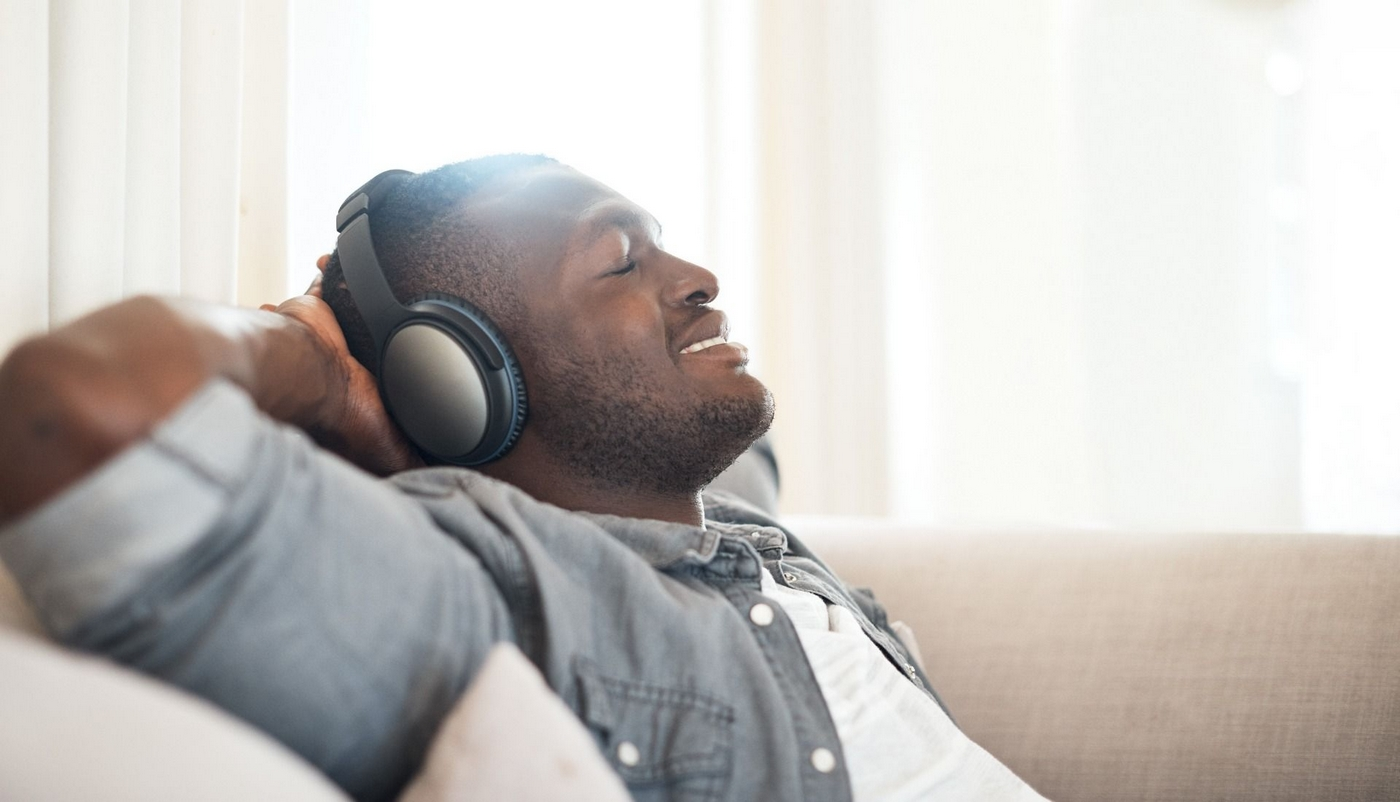 Man with headphones on sitting on couch