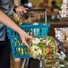 Woman picking up salad at grocery store