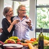 Couple smiling in kitchen while preparing dinner