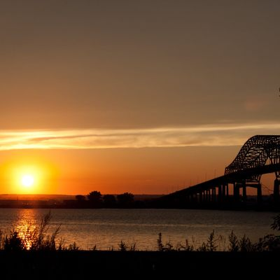 Outdoor image of a sunset over river with bridge in the image