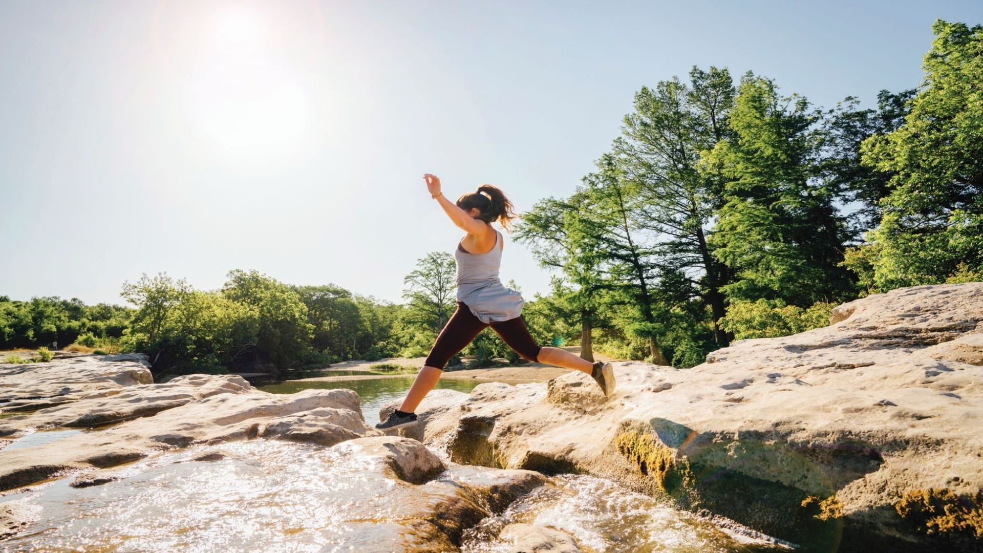 Image of a woman jumping over rocks on a hiking trail