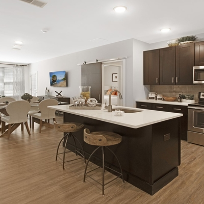 Interior image of apartment kitchen, island, wood dark cabinets and wood floors