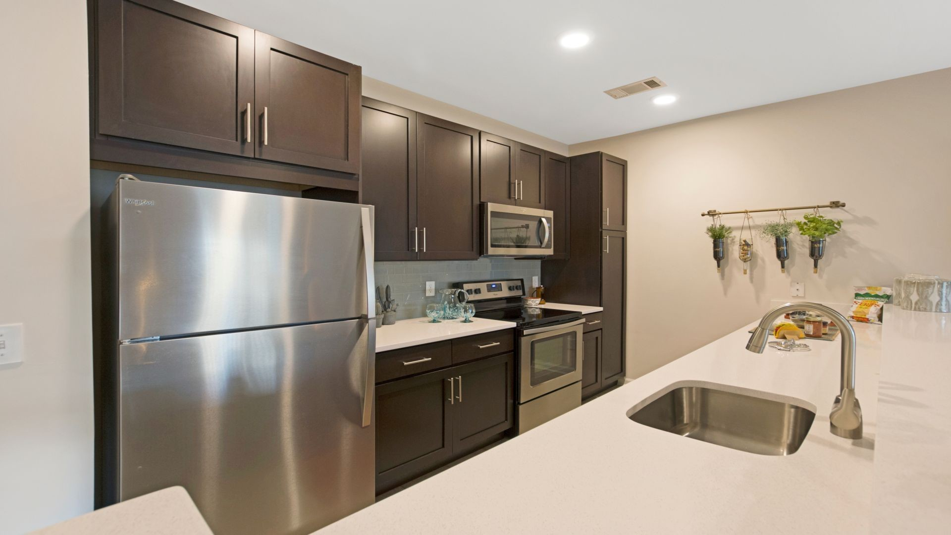 Interior kitchen image with stainless steel appliances dark wood cabinets and wood floors